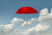 Red umbrella floating in clouds