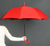 female hand holding red umbrella