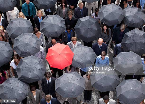 Red umbrella standing out in crowd of business people