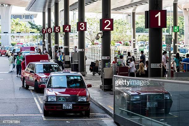 Red urban taxis pick up passengers at Hong Kong International Airport in Hong Kong China on Monday June 15 2015 The Hong Kong government in March...