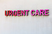 Signage for Urgent Care, red elevated letters against beige wall.  Exterior sign.  Urgent care is a commonly used part of the healthcare system in the United States.