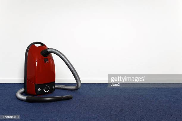 Red vacuum cleaner ion blue carpet in empty room