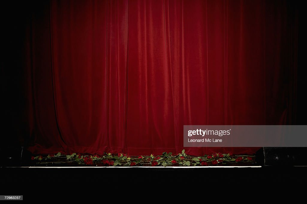 Red velvet theatre curtain, rose on stage : Stock Photo