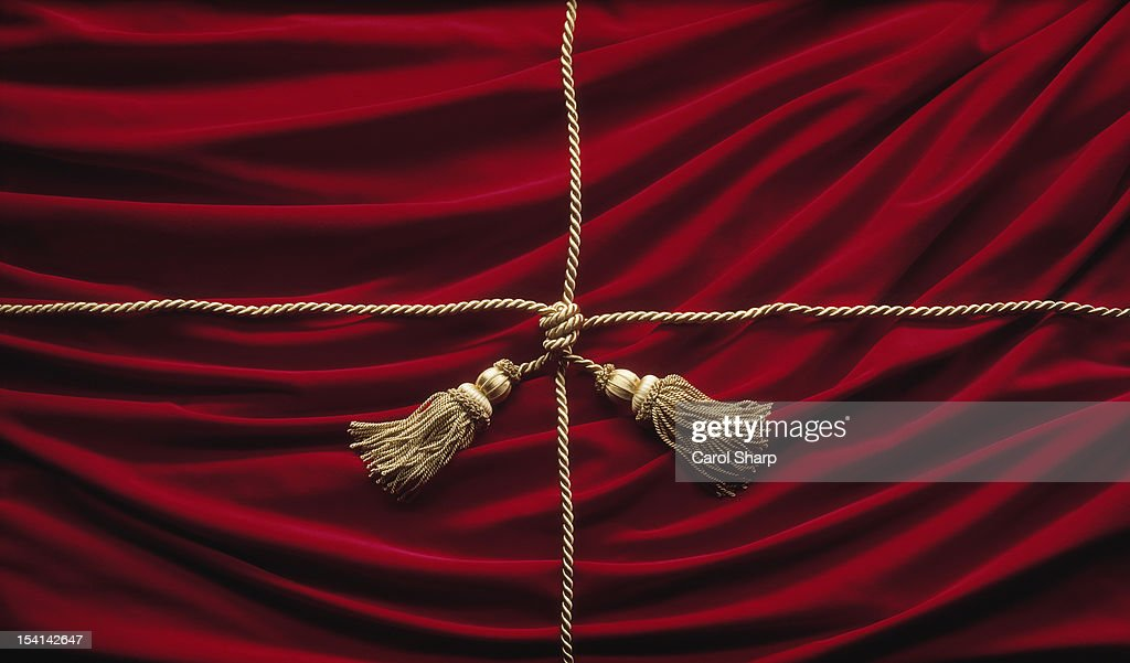 Red velvet theatre curtains with gold cord ties : Stock Photo
