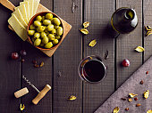 Red vine on wooden table served with green olives and cheese. Top view.