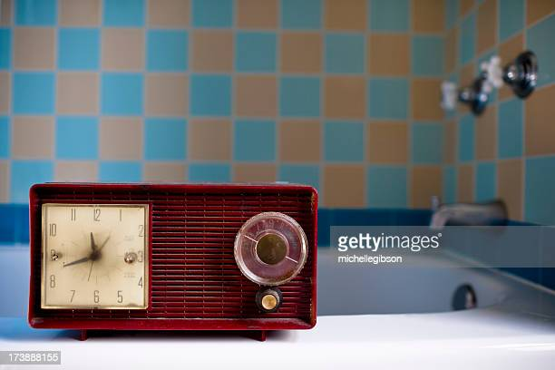 red vintage retro radio sitting on bath tub ledge