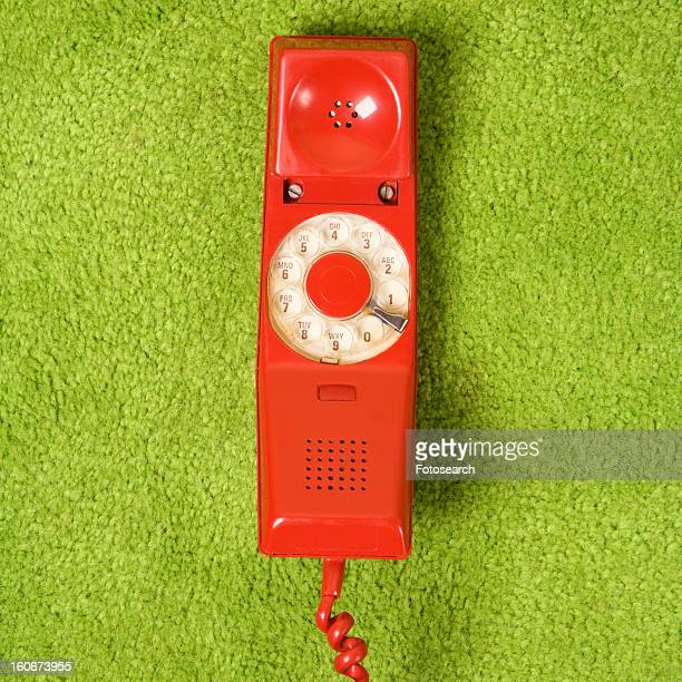 Red vintage rotary telephone receiver laying on 70's green carpet