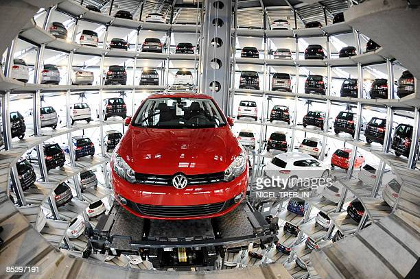 A red Volkswagen Golf and a white VW Scirocco are retrieved by an automated palette from a storage tower near the company's main factory in the...