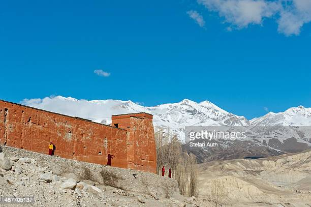 Red wall of a building with monks, Choede Gompa monastery, snow-capped mountains of Mustang Himal mountain range at back, Lo Manthang, Upper Mustang, Lo, Nepal