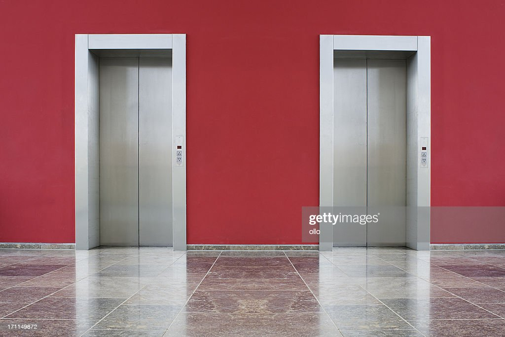 Red wall, two elevator doors