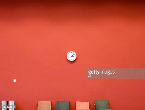 Rote Wand mit Uhr und vier Personen