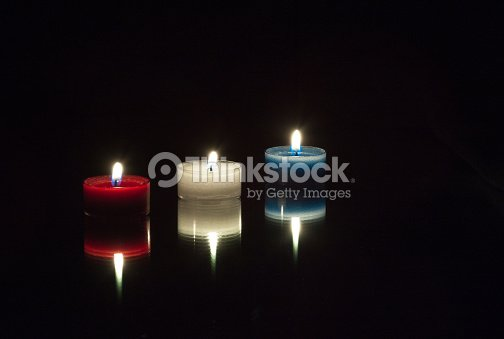 Red White Blue Candles On A Mirror With Lit Flames Stock Photo