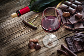 High angle view of a red wineglass and a selection of various chocolate bars, truffles and pralines shot on rustic wooden table. A wine bottle is at background and complete the composition. Copy space