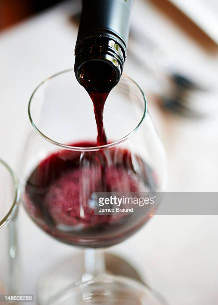Red wine being poured into glass.