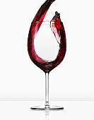 Red wine being poured into glass white backgroud