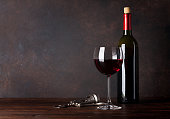Red wine bottle and glass in front of blackboard wall. With copy space for your text