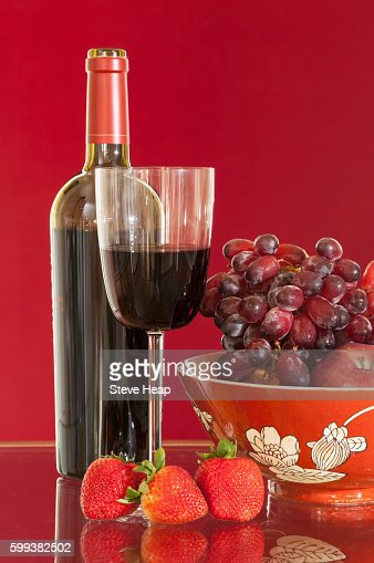 Red wine bottle and red wine in glass with red apples, grapes and strawberries in pottery bowl