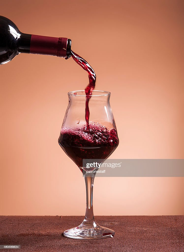 Red wine bottle pouring wineglass closeup : Stock Photo