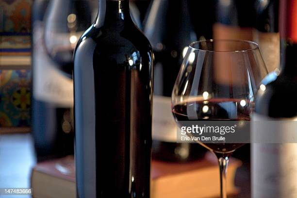 Red wine bottles and wine glass on table