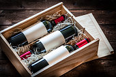 High angle view of a wooden box with three red wine bottles shot on rustic wooden table. The labels on the bottles are blank so you can put any design on them. Predominant color is brown. Low key DSRL