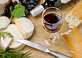 Red wine, Brie and Camembert cheeses with bread on the wood surface, studio shot