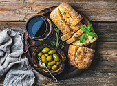 Wine snack set. Glass of red wine, green mediterranean olives, freshly baked ciabatta bread in dark wooden plate over rustic wooden background. Top view, horizontal composition