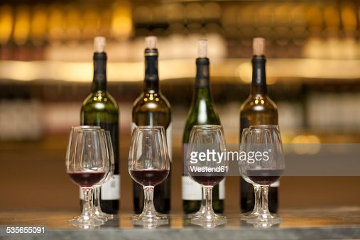 Red wine glasses and wine bottles on a counter of a wine cellar