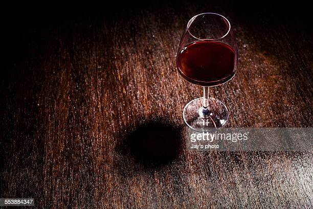 Red wine glasses on wood table with spot lighting