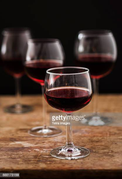 Red wine in glasses on wooden table, studio shot