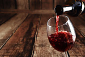 Red wine is poured from bottle to glass, wooden background