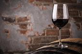 Glass of red wine standing on an oak barrel in a cellar