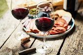 Red wine with charcuterie assortment on the background