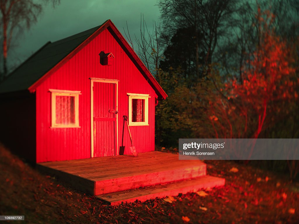Red wooden house in forest meadow : Stock Photo