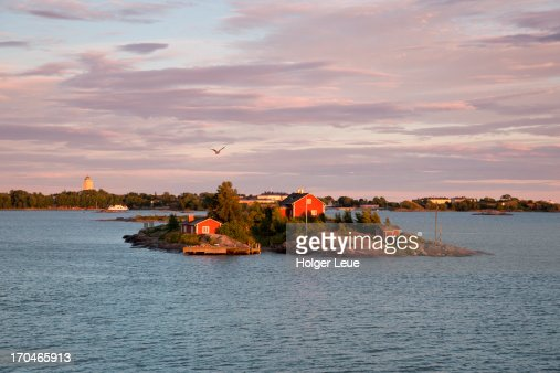 Red wooden house on small island in harbor