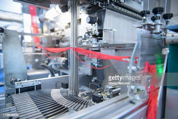 Red yarn passing through threading machine in textile mill