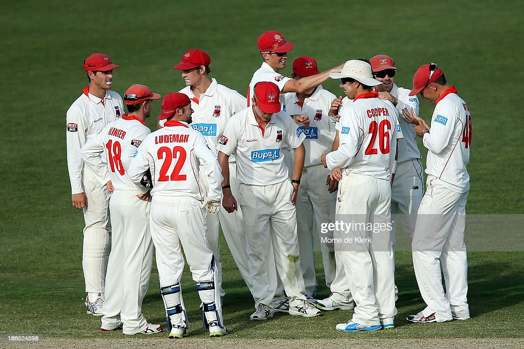 Redbacks players celebrate a wicket during day three of the Sheffield Shield match between the South Australia Redbacks and the Queensland Bulls at Glenelg Oval on November 1, 2013 in Adelaide, Australia.