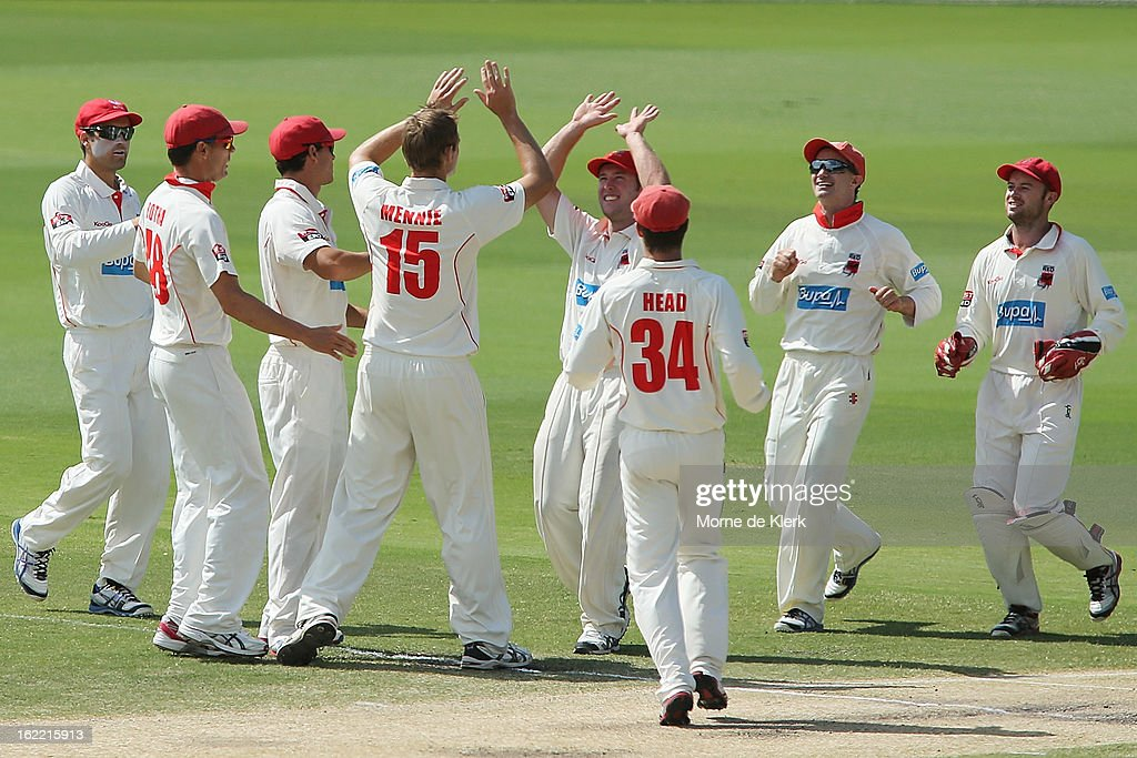 Redbacks players congratulate Joe Mennie after he got a wicket during day three of the Sheffield Shield match between the South Australian Redbacks and the New South Wales Blues at Adelaide Oval on February 21, 2013 in Adelaide, Australia.