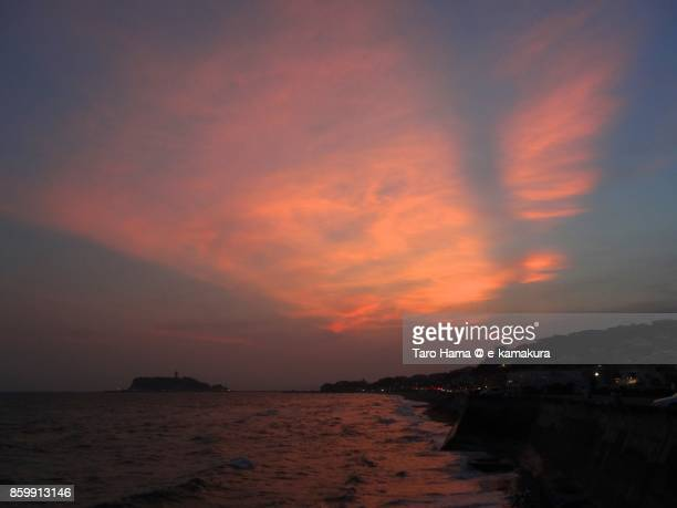 Red-colored sunset clouds on Mt. Fuji, Enohsima Island and the beach in Kamakura city in Kanagawa prefecture in Japan