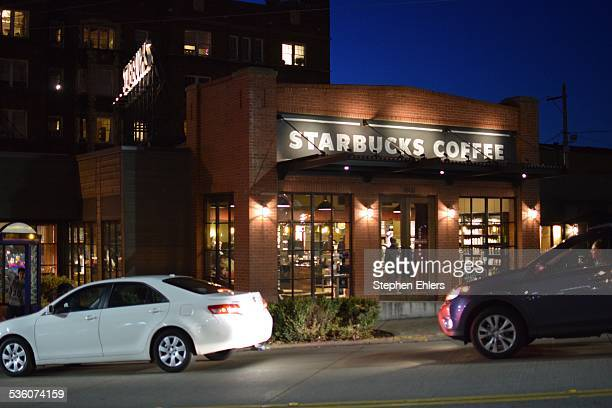 A redesigned Starbucks store with a new brown logo in the Capitol Hill neighborhood of Seattle Washington Lights shine on the store and cars pass at...