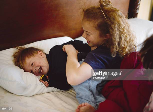 A redhaired big sister tickles her little brother on a bed