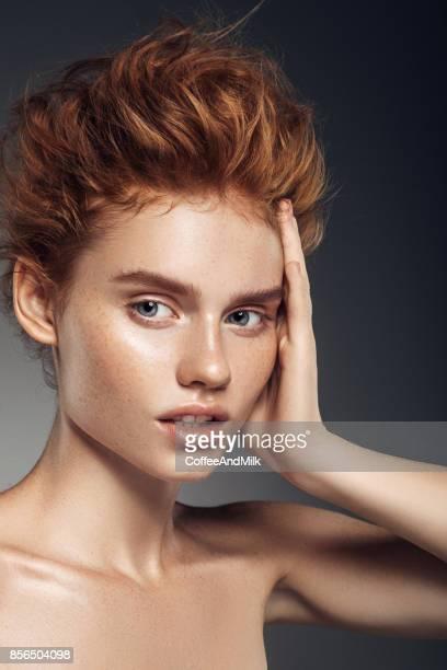 Fille rousse avec boucles et maquillage à la mode