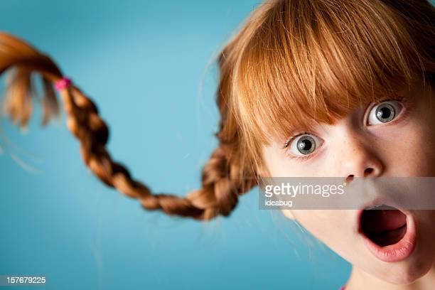 Red männlichen Mädchen mit nach oben, geflochtener Zopf und Look der Überraschung