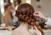 Beautiful, with long, red-haired hairy girl, hairdresser weaves a French braid, close-up in a beauty salon. Professional hair care and creating hairstyles.