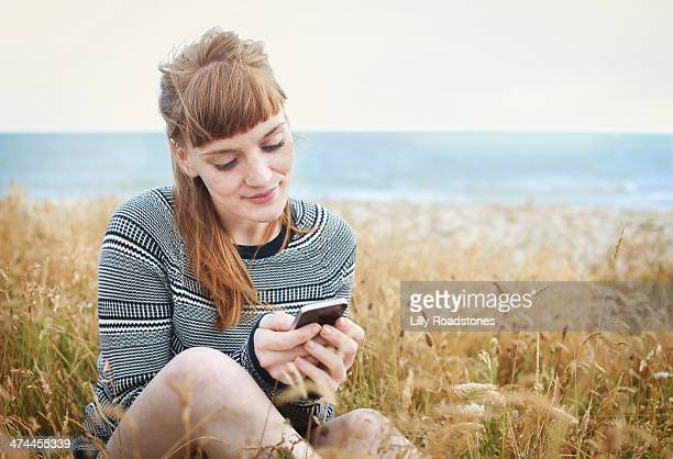 Red-haired woman texting by the sea