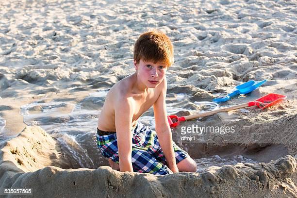 Redhead boy on beach making a sand castle