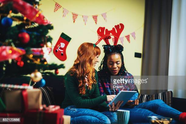 Redhead girl and her African friend enjoy Christmas together at home