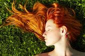 beautiful young redhead girl relaxing lying on the grass