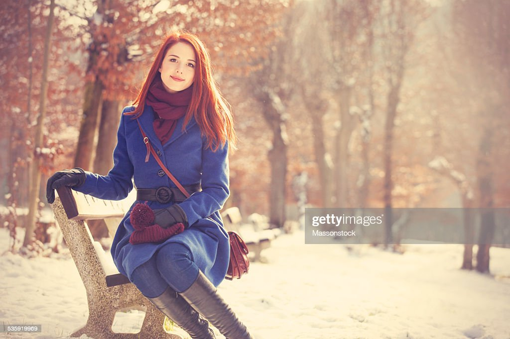 Redhead girl sitting on a bench in the winter park. : Stock Photo