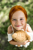 close-up portrait of adorable red haired girl hugging teddy bear and smiling at camera