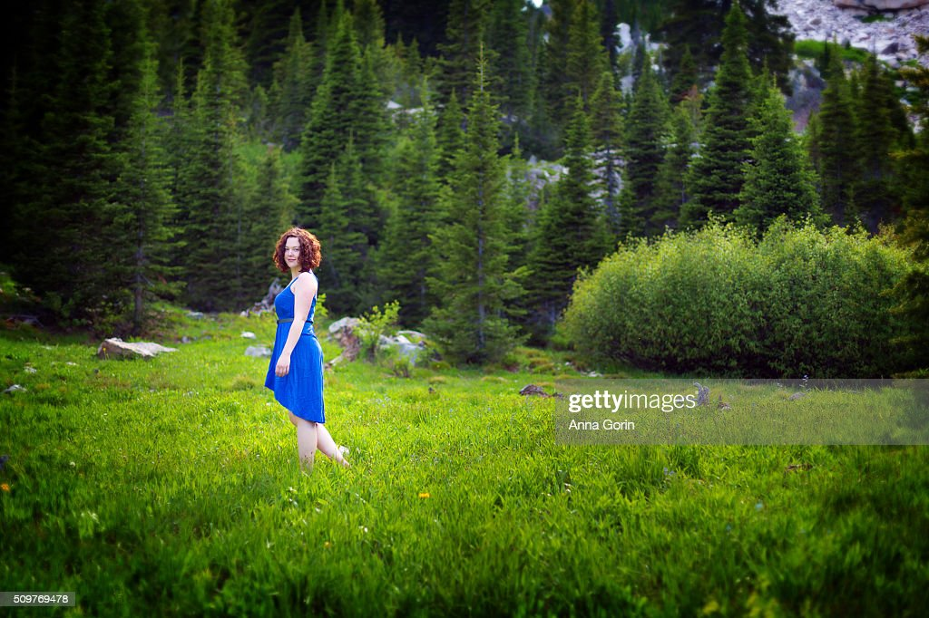 Redhead in blue dress alone in lush meadow surrounded by forest, looking at camera